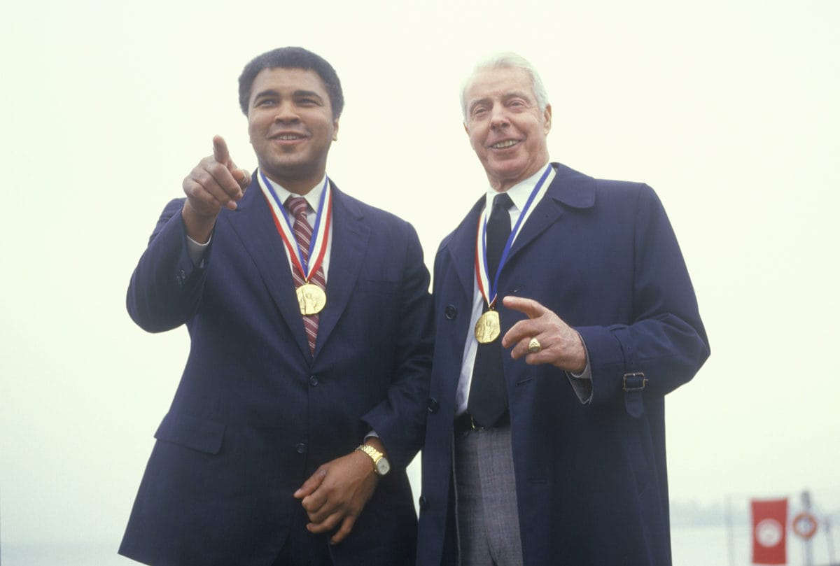Muhammed Ali and Joe DiMaggio wearing gold medals, Ellis Island, NY